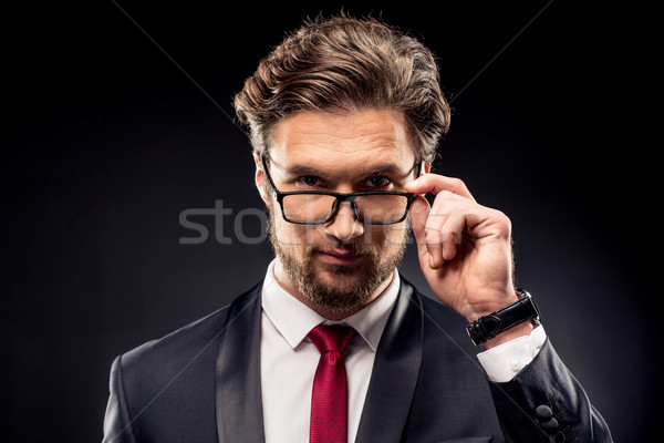 Businessman adjusting eyeglasses Stock photo © LightFieldStudios
