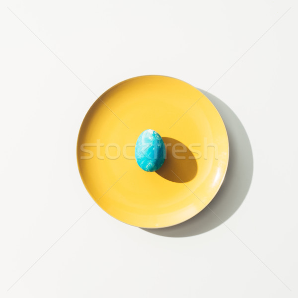 top view of shabby blue easter egg on yellow plate, on white Stock photo © LightFieldStudios