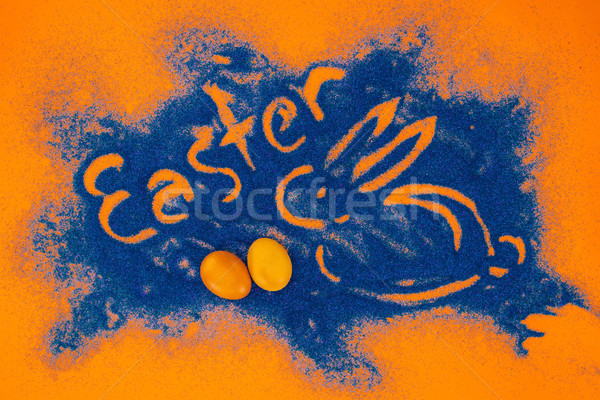 top view of easter sign with rabbit made of blue sand with painted eggs on orange Stock photo © LightFieldStudios