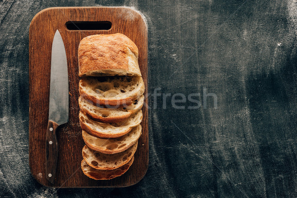Top view of arranged pieces of ciabatta on cutting board with knife on dark surface with flour Stock photo © LightFieldStudios