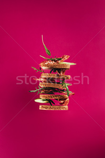 close up view of levitating sandwiches with bacon pieces and arugula isolated on pink Stock photo © LightFieldStudios