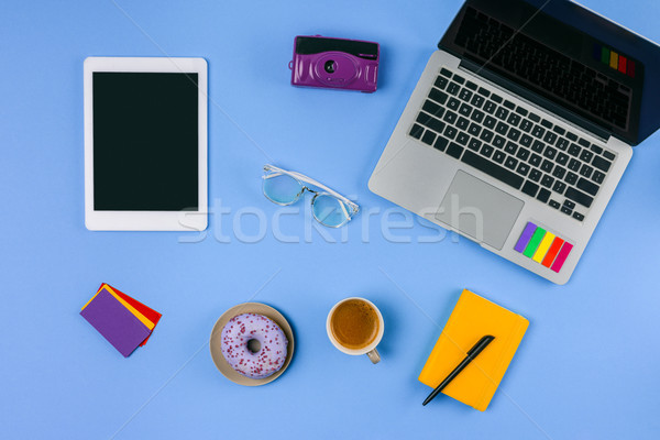 top view of laptop, digital tablet, cup of coffee with doughnut and camera on blue  Stock photo © LightFieldStudios