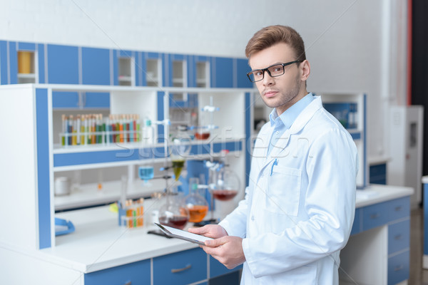 Young man scientist in eyeglasses and lab coat holding digital tablet and looking at camera  Stock photo © LightFieldStudios