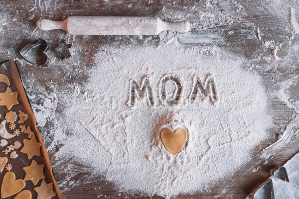 Stock photo: 'Top view of uncooked heart shaped cookie and word mom written in flour, Mothers day concept