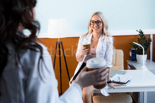 smiling professional doctors drinking coffee in cabinet on break Stock photo © LightFieldStudios