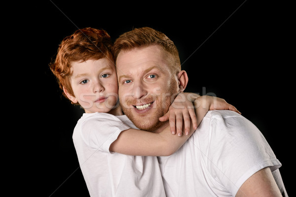 Happy father with son hugging and smiling at camera isolated on black  Stock photo © LightFieldStudios