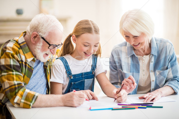 Happy girl with grandfather and grandmother sitting at table and drawing together Stock photo © LightFieldStudios