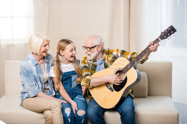 Cute happy girl with grandparents sitting together on sofa and playing acoustic guitar Stock photo © LightFieldStudios
