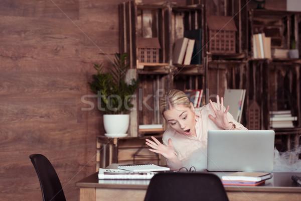 Scioccato giovani imprenditrice guardando laptop fumo Foto d'archivio © LightFieldStudios