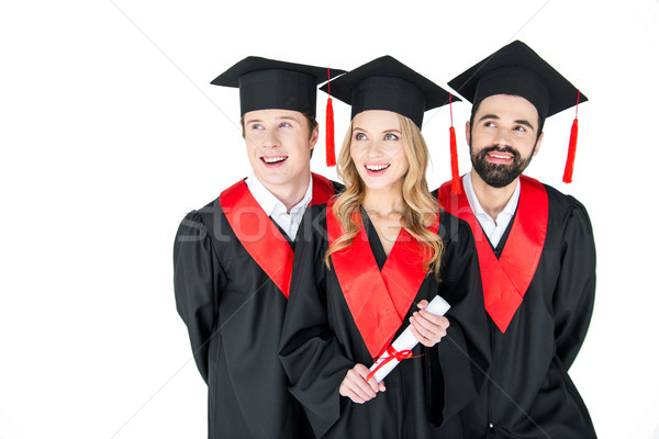 Happy students in mortarboards and graduation gowns looking away on white Stock photo © LightFieldStudios