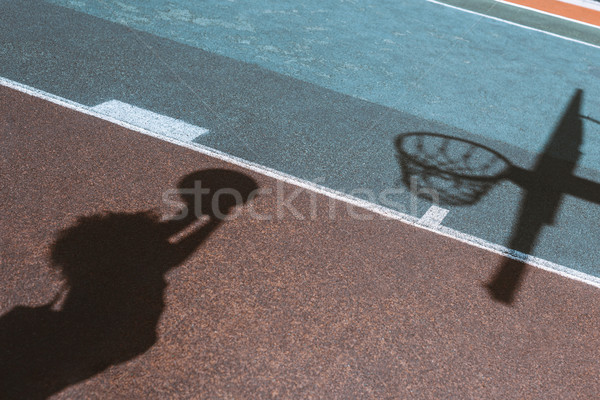 Shadow of woman throwing ball Stock photo © LightFieldStudios