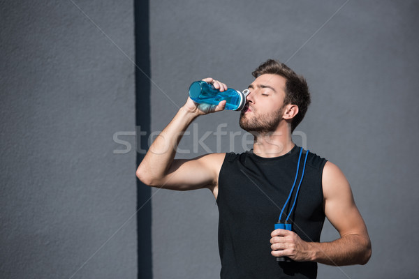 man with skipping rope drinking water Stock photo © LightFieldStudios