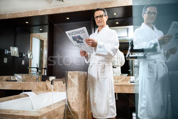 üzletember fürdőköpeny olvas újság visel hotel Stock fotó © LightFieldStudios