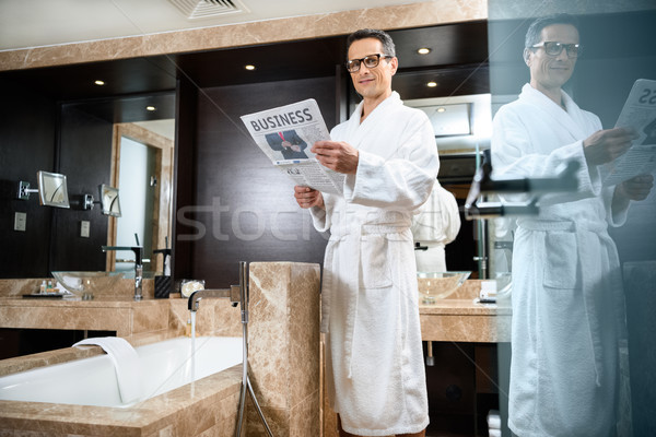 Zakenman badjas lezing krant hotel Stockfoto © LightFieldStudios
