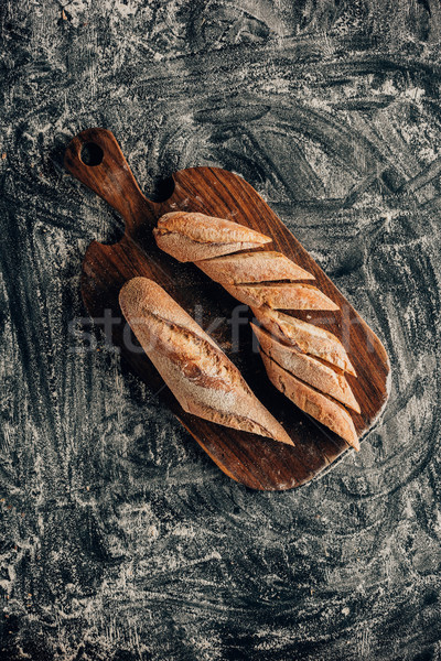top view of arranged pieces of french baguette on cutting board on dark surface with flour Stock photo © LightFieldStudios