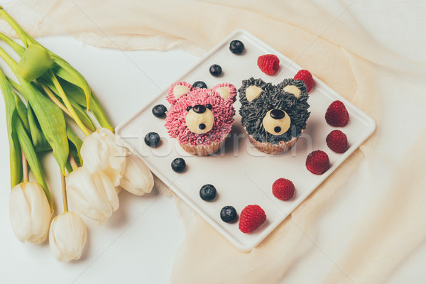 close-up view of delicious muffins in shape of bears, fresh berries and tulip flowers  Stock photo © LightFieldStudios