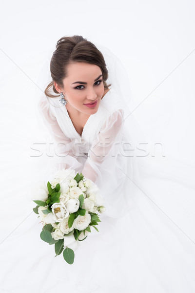 Stock photo: smiling bride in traditional white dress holding wedding bouquet, isolated on white