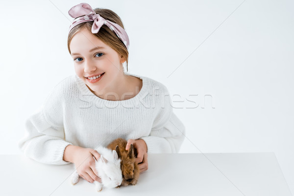 beautiful girl holding adorable furry rabbits and smiling at camera on white Stock photo © LightFieldStudios