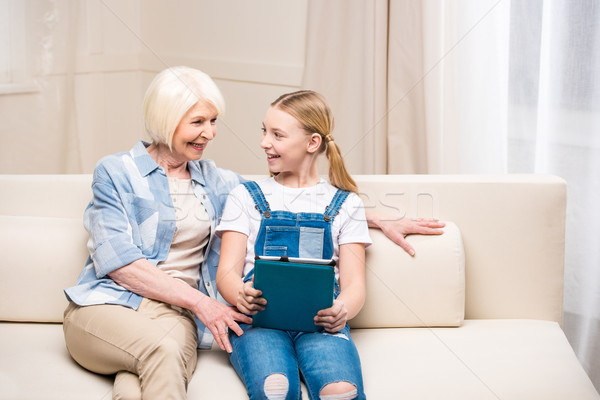 Smiling grandmother and granddaughter sitting on sofa with digital tablet and looking at each other  Stock photo © LightFieldStudios