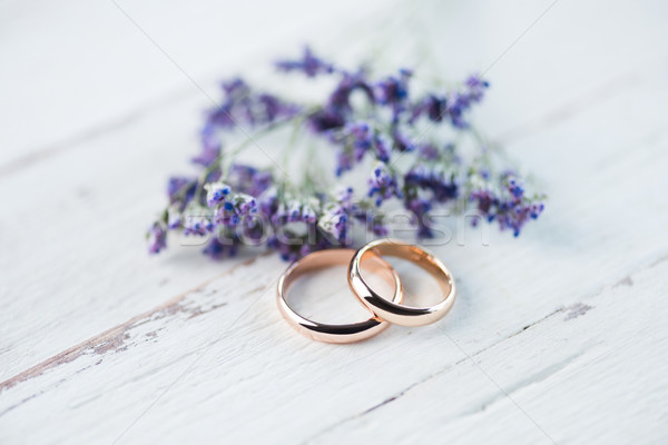 Close-up view of golden wedding rings and beautiful small blue flowers on wooden tabletop Stock photo © LightFieldStudios