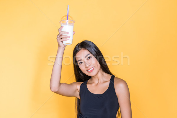 Asian woman holding milkshake Stock photo © LightFieldStudios