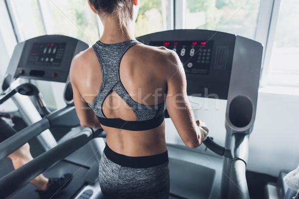 Vrouw tredmolen achteraanzicht cardio gymnasium Stockfoto © LightFieldStudios