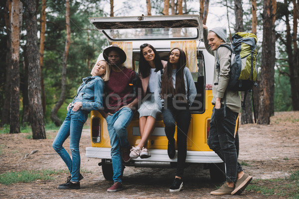 Stock photo: multiethnic travelers near minivan in forest