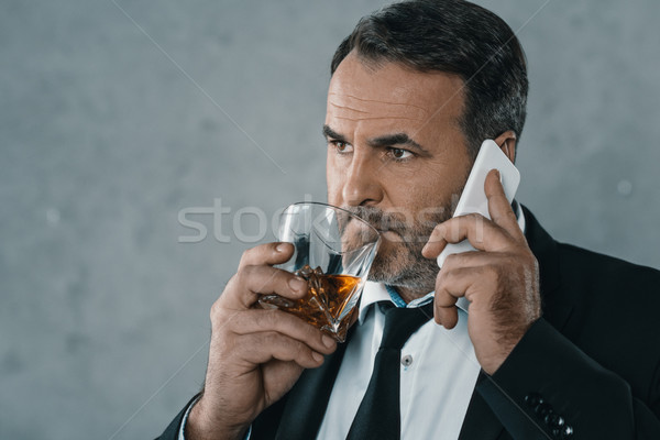 businessman talking by phone with whiskey Stock photo © LightFieldStudios