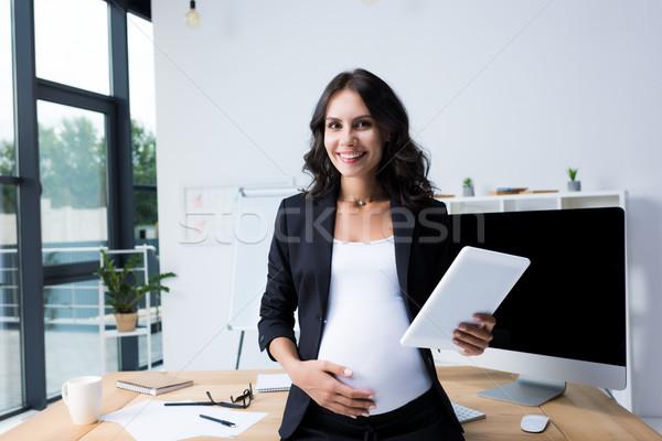 Incinta imprenditrice tablet moderno ufficio guardando Foto d'archivio © LightFieldStudios