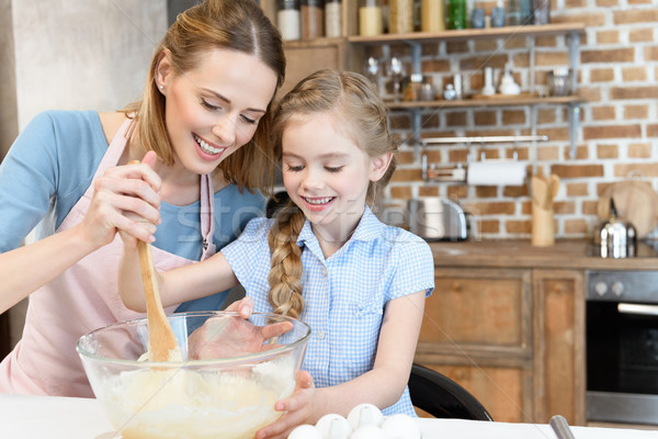 Happy mother and daughter preparing dough in glass bowl at kitchen Stock photo © LightFieldStudios