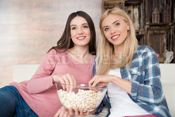 Szczęśliwy młodych kobiet posiedzenia sofa jedzenie popcorn Zdjęcia stock © LightFieldStudios