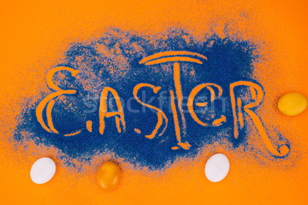 top view of easter sign made of blue sand with chicken eggs on orange Stock photo © LightFieldStudios