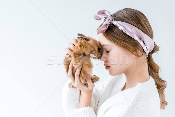 side view of beautiful little girl holding furry rabbit isolated on white Stock photo © LightFieldStudios