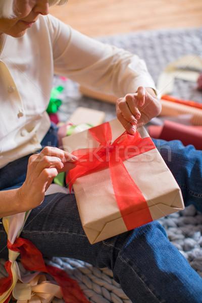 Woman wrapping christmas present Stock photo © LightFieldStudios