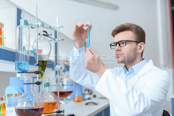 Young man scientist in eyeglasses and white coat examining test tube in laboratory Stock photo © LightFieldStudios