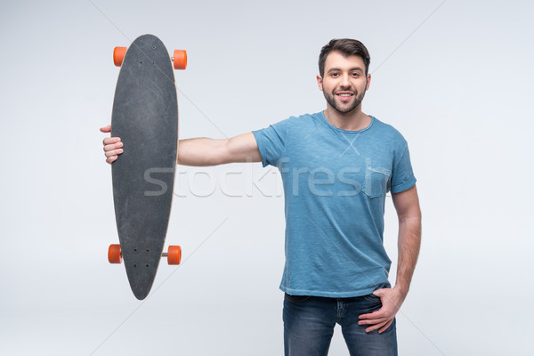 portrait of smiling man holding skateboard in hands on white Stock photo © LightFieldStudios