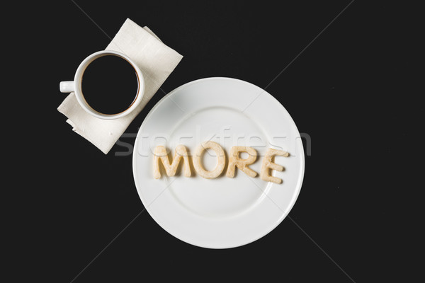 top view of more word  made from cookie dough on plate with coffee cup isolated on black Stock photo © LightFieldStudios