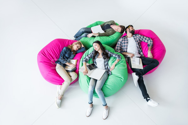 tired students sleeping in beanbag chairs with books in studio on white  Stock photo © LightFieldStudios