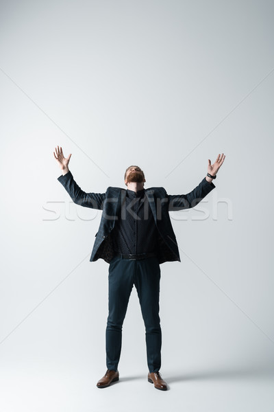 stylish bearded man in elegant suit with hands up on white Stock photo © LightFieldStudios