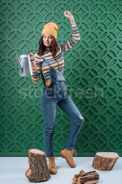 Woman in autumn outfit with watering can Stock photo © LightFieldStudios