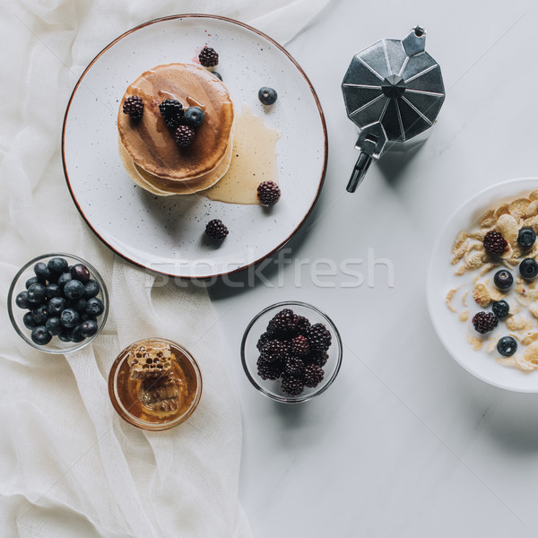 top view of fresh homemade pancakes with honey and berries, coffee pot and muesli with milk on grey Stock photo © LightFieldStudios