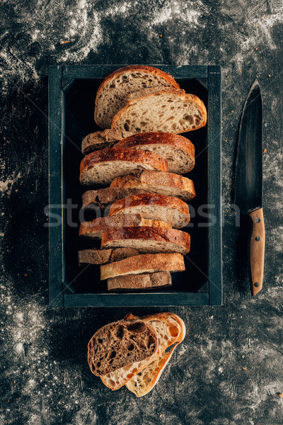 Stock photo: top view of arranged pieces of bread in wooden box and knife on dark tabletop with flour