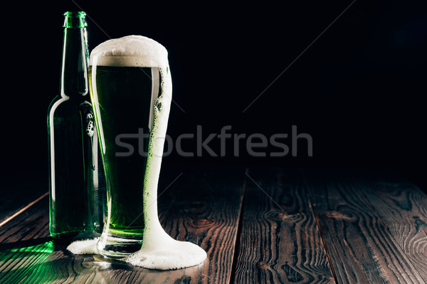 glass and bottle of green beer with foam on table, st patricks day concept Stock photo © LightFieldStudios