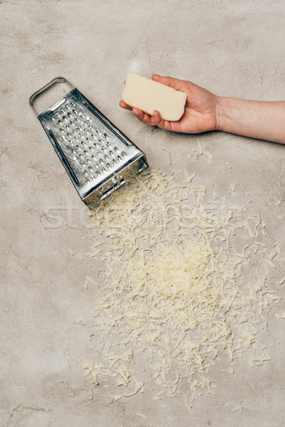 Close-up view of hand holding cheese by grater on light background Stock photo © LightFieldStudios
