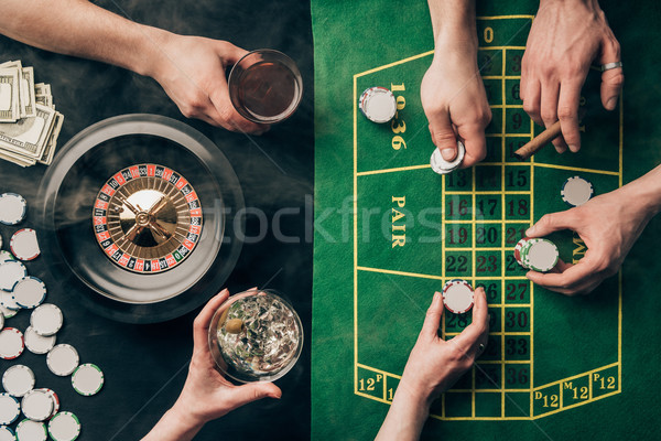 People drinking alcohol while playing roulette by casino table Stock photo © LightFieldStudios