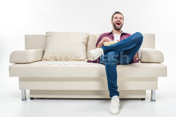 Man sitting on couch with popcorn Stock photo © LightFieldStudios