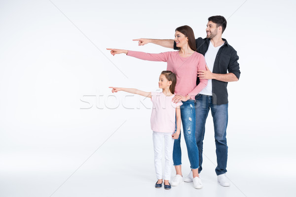 Happy young family standing together and pointing away with fingers on white Stock photo © LightFieldStudios