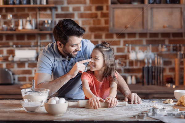 'Happy father and daughter having fun while cooking together Stock photo © LightFieldStudios