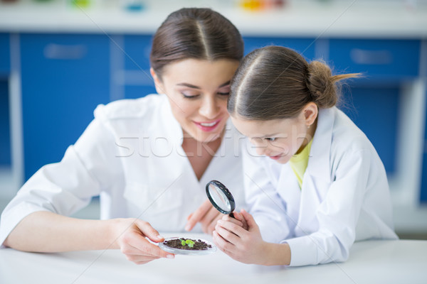 Smiling teacher and little student scientists looking at green plant in soil through magnifier Stock photo © LightFieldStudios