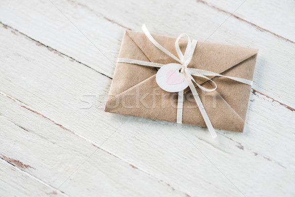 kraft envelope with teg with heart and ribbon on white wooden tabletop, invitation card wedding conc Stock photo © LightFieldStudios